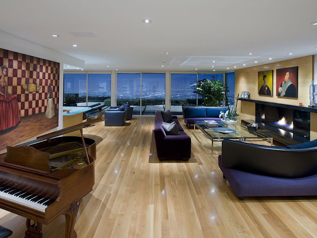 Picture of large living room with modern furniture, wooden piano and beautiful views of the city at night