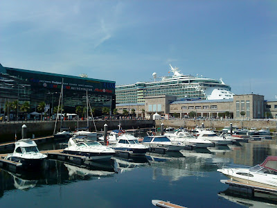 "The cruise ship ""Independence of the Seas"" docked in the port of Vigo, near the ferry terminal and the A Laxe shopping mall"