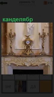 Сверху на камине стоят два канделябра и часы