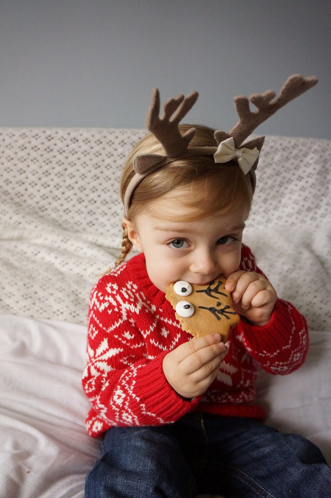 christmas toddler portrait with reindeer antlers and eating reindeer biscuit