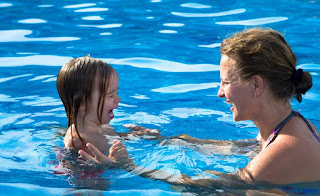 Image of an upset toddler and his teacher in the water: This article is about Toddler Swimming