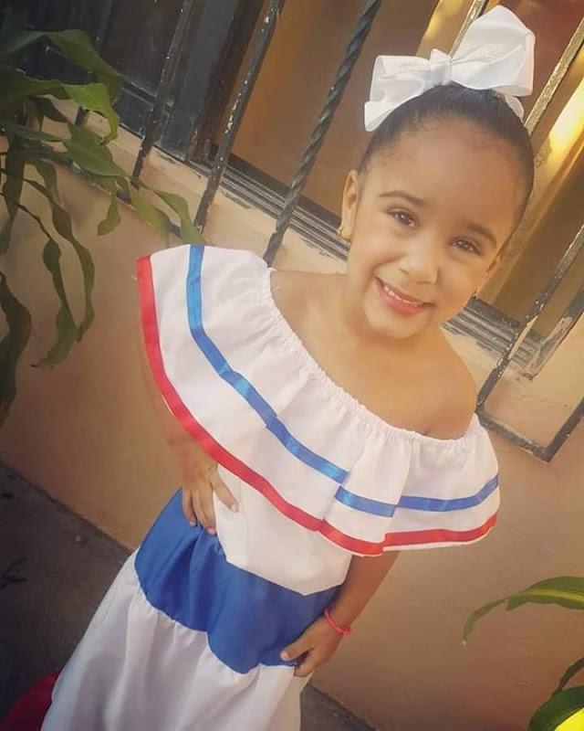 Su sonrisa muestra el orgullo Dominicano, vistiendo nuestros símbolos patrios.