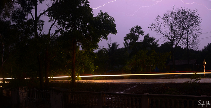 Image of lightning striking the sky during a thunderstorm while cars drive on the roads in Goa