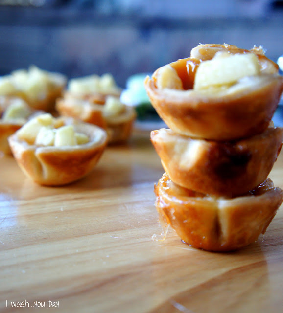 A close up of three stacked mini apple pies in front of more mini apple cupcake pies.