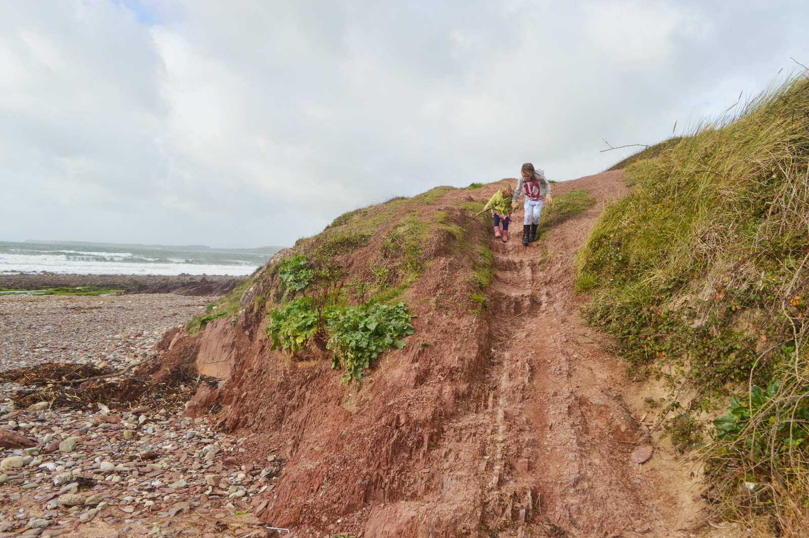 Girls Climbing Down Rocks at Manorbier Beach, Pembrokeshire, Wales