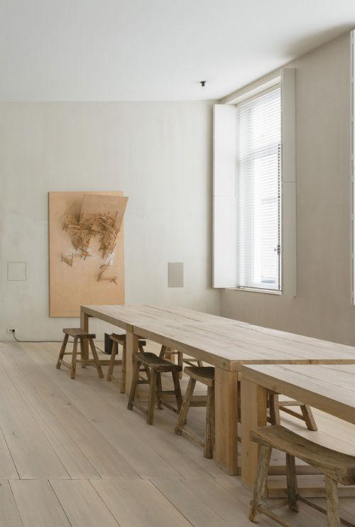 Leuchtend Grau: Im Wohnzimmer stehen zwei rustikale Holztische mit Holzhockern.