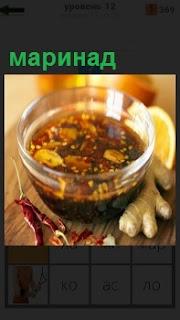 В прозрачной стеклянной чаше приготовленный маринад, рядом остались ингредиенты в виде перец красный, хрен и другие