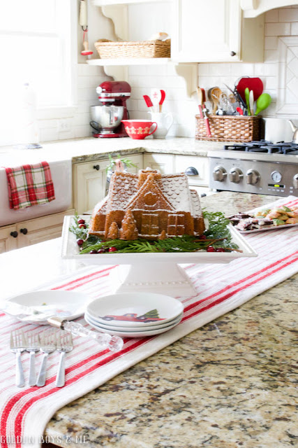 Gingerbread house cake displayed in farmhouse style kitchen with red and white Christmas decor