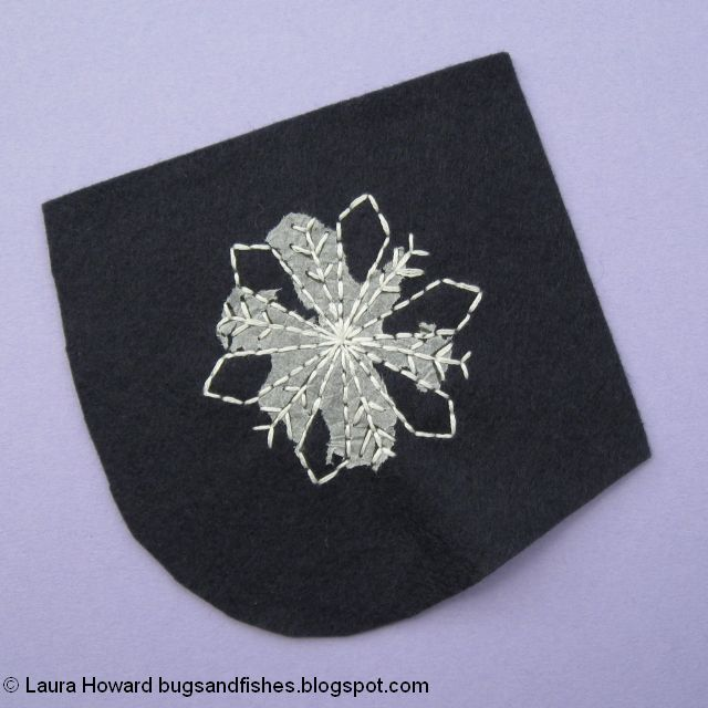 tear away the tissue paper from the embroidered snowflake