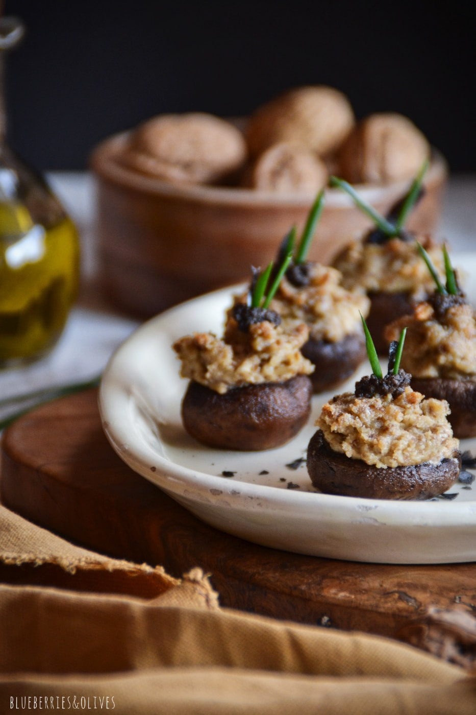 STUFFED MUSHROOMS WITH WALNUT TRUFFLE PÂTÉ IN A WHITE PLATE, DARK BACKGROUND