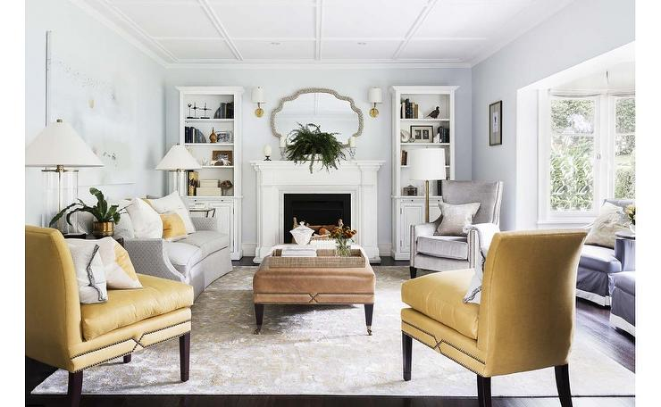 White fireplace flanked by white freestanding bookshelves.