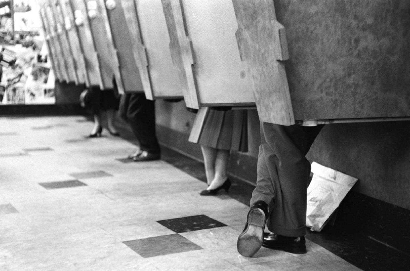 Customers in listening booths while standing up. 1958.