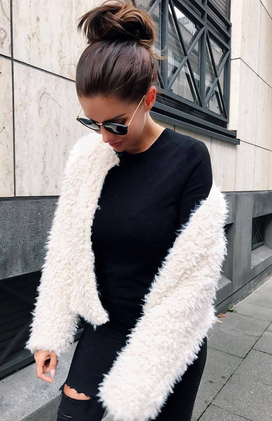 cozy fall outfit idea / black top + white fur jacket + ripped jeans