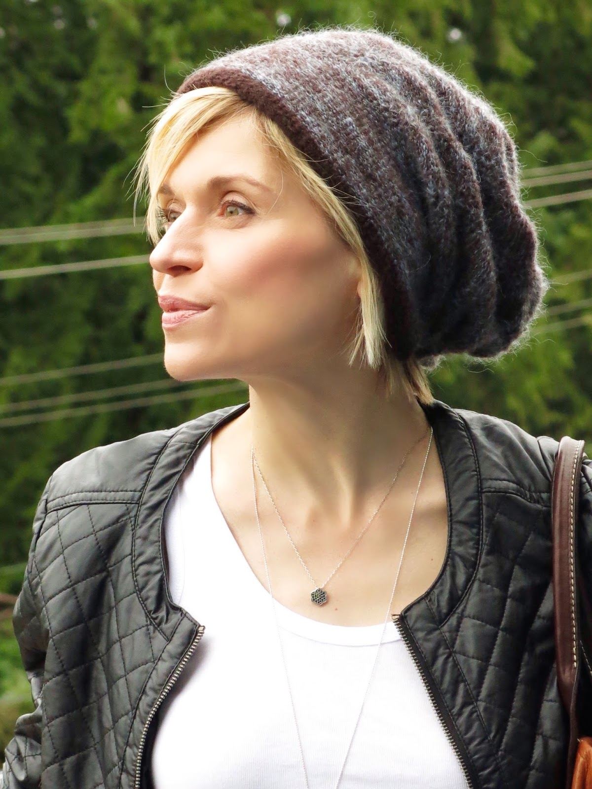 white tank, quilted faux-leather jacket, and woolen beanie