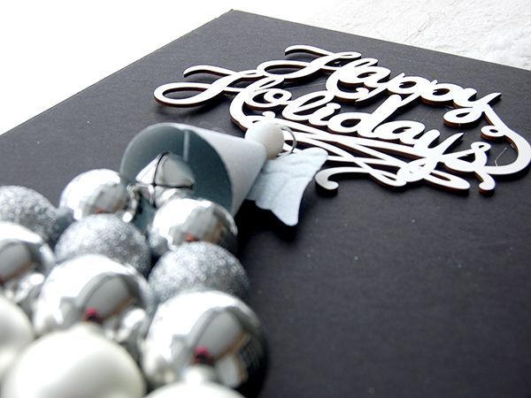White Happy Holidays sign, white glitter ornament, silver ornament bulbls upclose