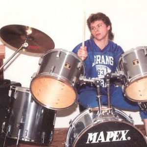 A young Pauly playing drums
