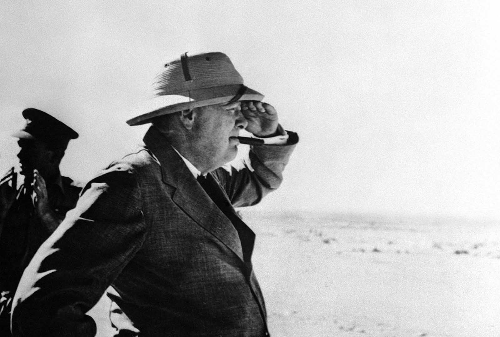 During his stay in the Middle East, Britain's Prime Minister Winston Churchill paid a visit to the Alamein area, meeting brigade and divisional commanders, visiting a gun site, and inspecting personnel of Australian and South African divisions, on August 19, 1942 in the western desert.
