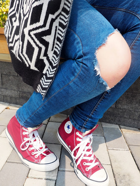 Kicking Back - outfit close up details, of black and white cardigan print, ripped skinny jeans, and red high top Converse sneakers