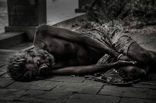 homem seminu dormindo no meio da calçada