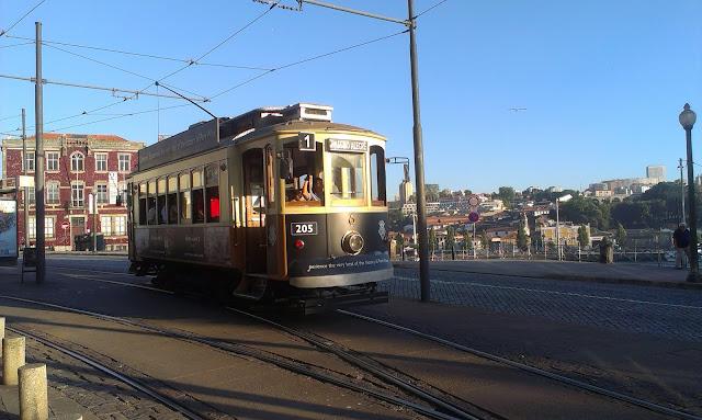 Turystyczny wagon tramwajowy przewozi turystów wzdłuż brzegu Douro aż nad ocean.