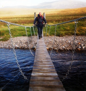 A man crossing a narrow footbridge with chains for hand holds