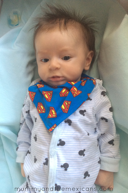 How We Coped With The End Of Maternity Leave With An 8-Week-Old Baby - Image Shows Baby Lying In Cot Wearing A Superman Bandana Bib