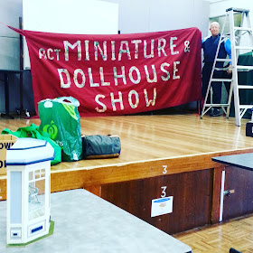 Man putting up a fabric banner for the ACT Miniature & Dollhouse Show on a stage in a community hall. Boxes and bags and unpacked miniatures lie on the stage and table in front of it.