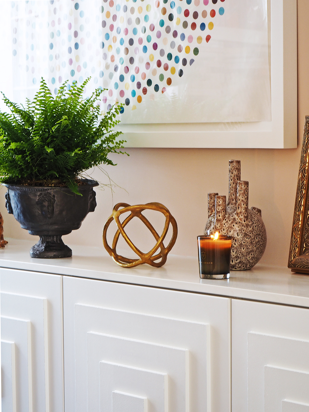 My Summer Dining Room - French For Pineapple Blog - damien hirst valium print above sideboard with stepped panelled doors with boston fern in an urn planter and gold orb decorative object
