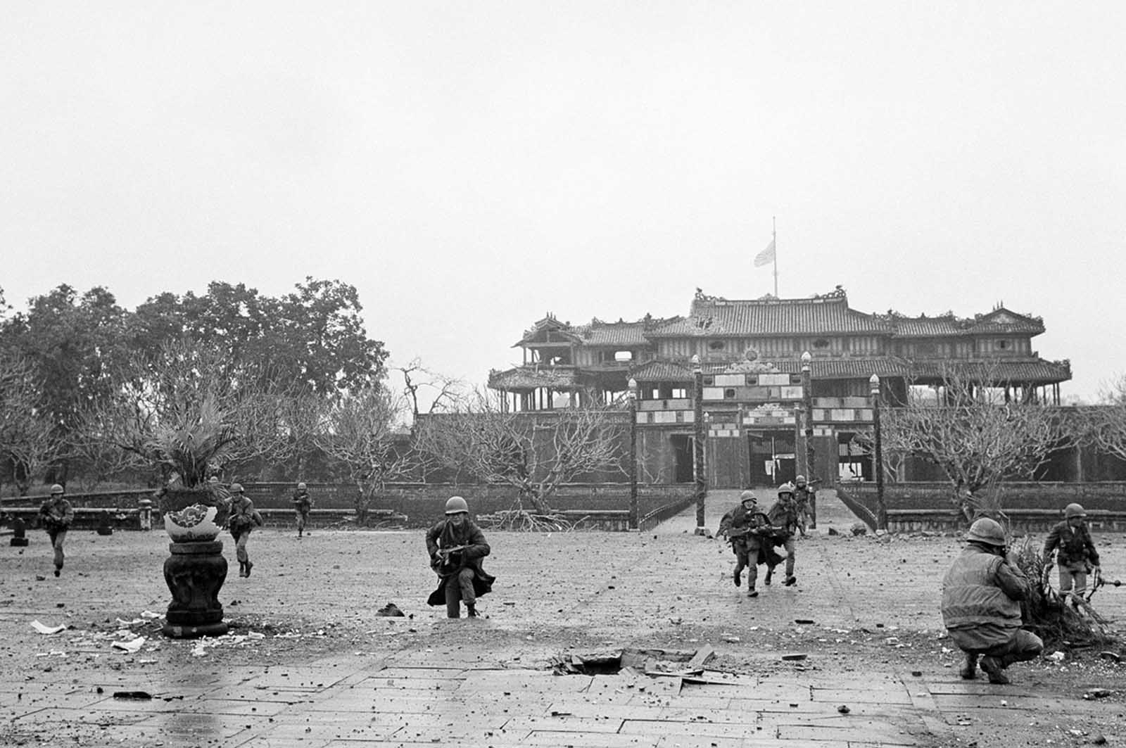 U.S. Marines and Vietnamese troops move through the grounds of the Imperial Palace in the old citadel area of Hue, Vietnam, on February 26, 1968, after seizing it from Communist hands. The heavy damage was the result of the artillery, air, and mortar pounding the area received for 25 days while the Viet Cong/NVA held the area.
