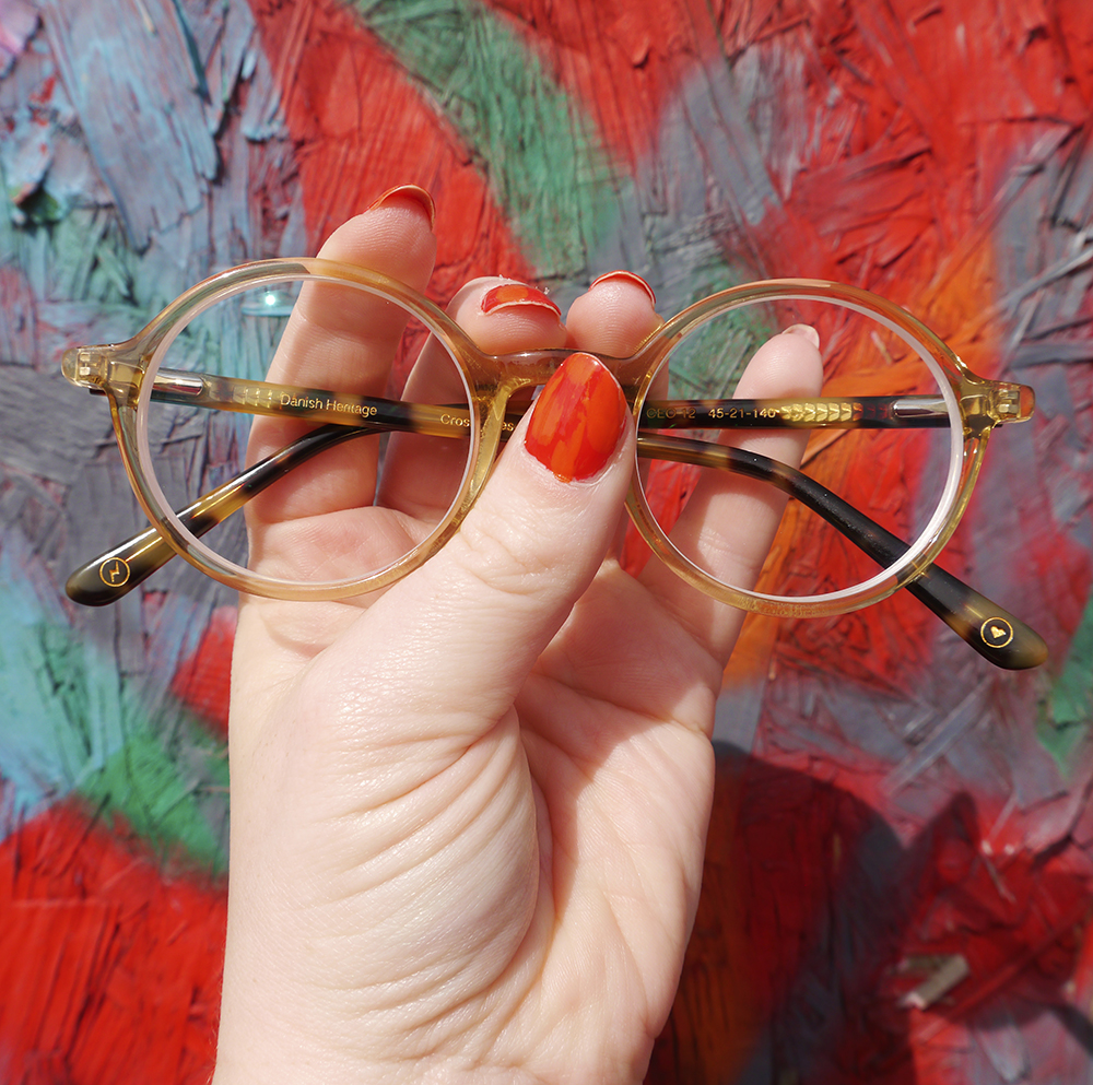 Hand with red nail polish holding CrossEyes Edinburgh Circle Frame Glasses