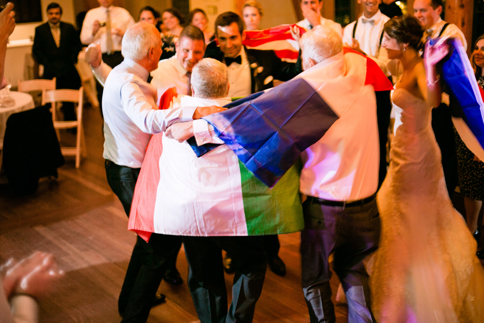 a group of italian french and american wedding attendees dance with their native flags in celebration of their families uniting