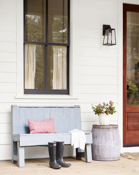 Charming blue bench on porch with white clapboard siding and beautiful modern farmhouse style inspiration on Hello Lovely Studio
