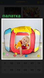 Маленькая девочка находится в детской палатке, играет шариками