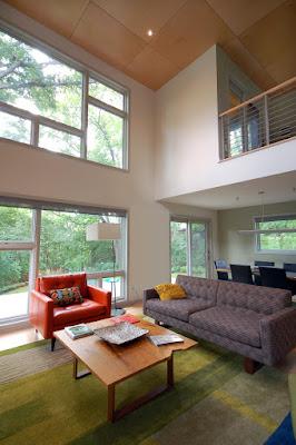 ห้องนั่งเล่นหน้าบ้านเน้นโซฟาหลากสีและโต๊ะไม้สวย