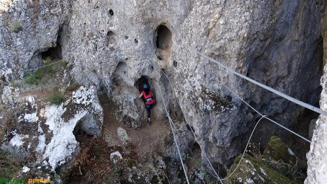 Entrando en la cueva que da acceso al puente en la ferrata Huerta de Rey.