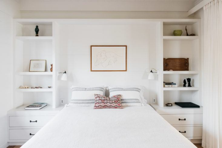 Beautiful bedroom with built-in shelves flanking bed in beautiful oceanfront cottage on Maui - found on Hello Lovely Studio