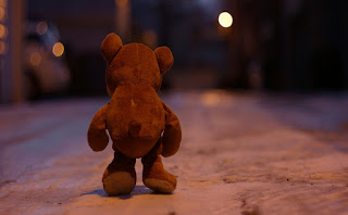 lonely-teddy-bear-walking-alone-in-street-at-night-image.jpg