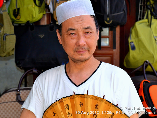 street portrait, headshot, China, Xi'an, Hui Muslims, Hui Muslim man, taqiyah, white skullcap, kufi, Chinese fan