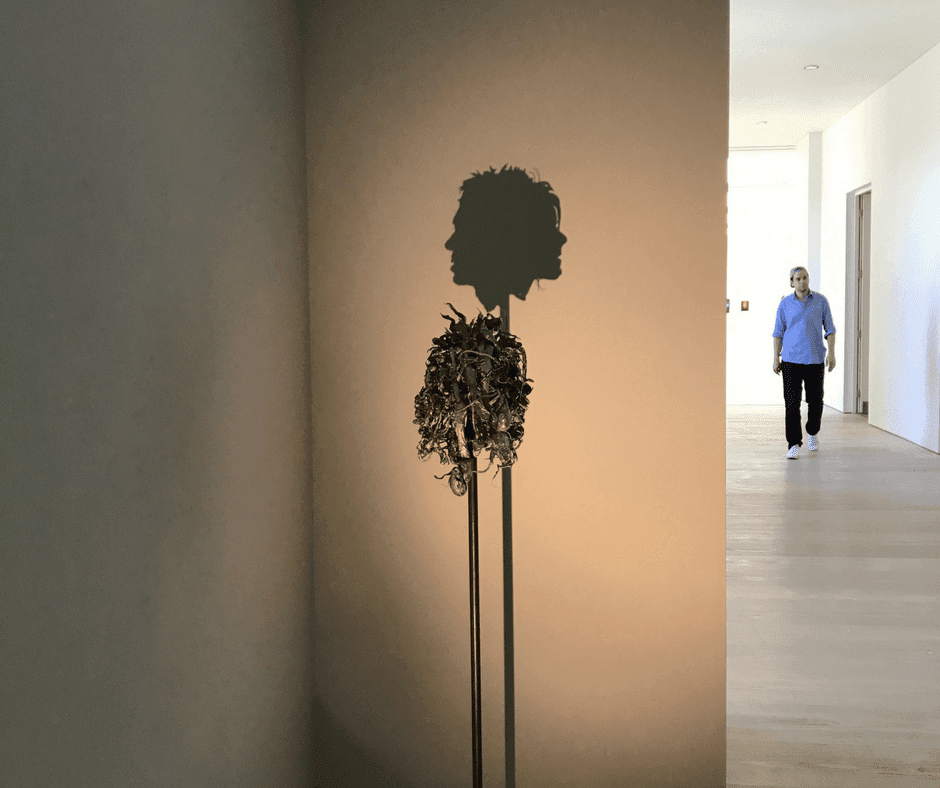 Piece of metal art that has a shadow of a man and a woman's head.
