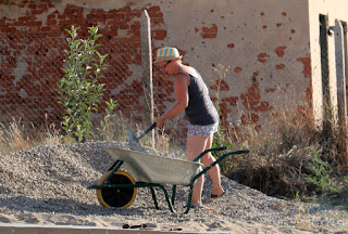 A getting stuck in to loading a wheelbarrow with stones