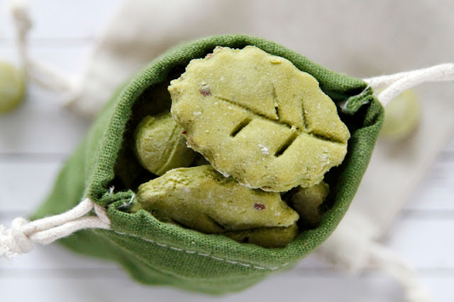 Homemade dog treats shaped like green leaves with a green drawstring treat bag
