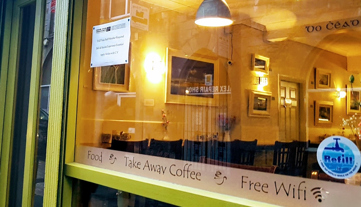 Front window of an Irish cafe with framed artworks on display along the side wall.Hot food.  Takeaway coffee.  Free wifi.