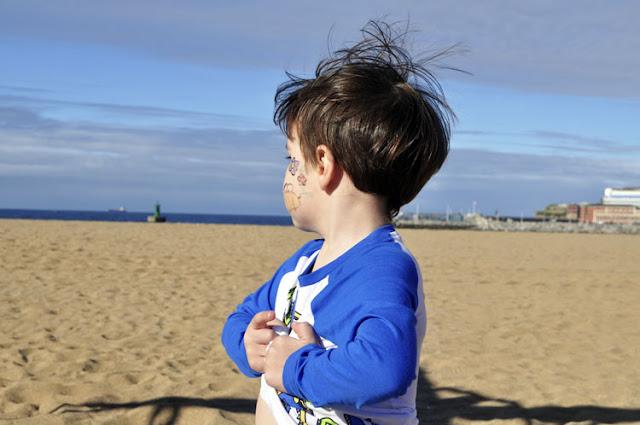el viento le revuelve el cabello, en la mejilla lleva pintadas flores y abajas, mira el mar y se agarra la camiseta