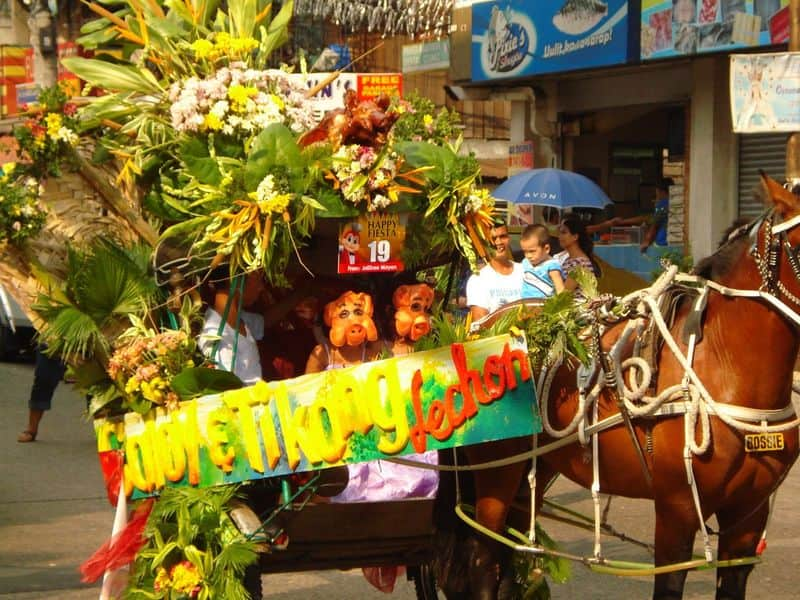 People in lechon costumes riding a float during the La Loma Lechon Festival