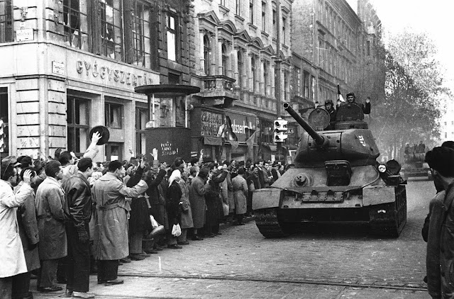 A black and white photo of crowds cheering Hungarian troops during the 1956 Revolution.