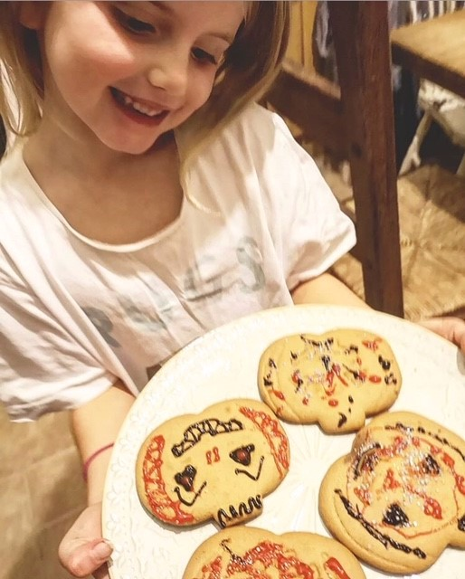 Little girl smiling and holding a plate full of pumpkin shaped biscuits that have been iced