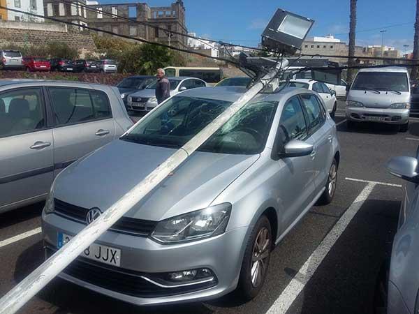 En Arucas el fuerte viento tira un poste eléctrico y cae encima de un coche