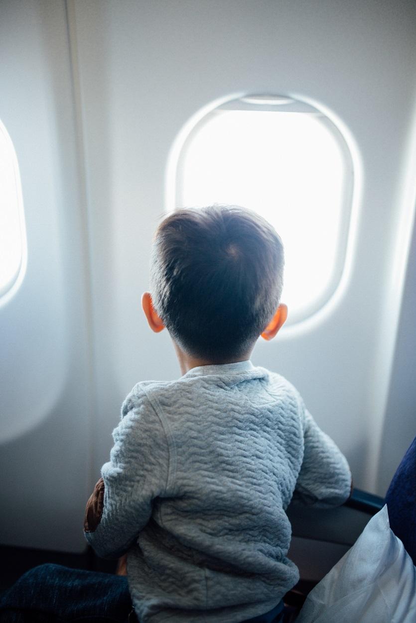Menino encantado no avião, encarando a janela