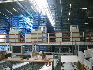 Imagem mostra mercadorias empilhadas em paletes com empilhadeira, concebidas por um Warehouse Management System( WMS), em português - literalmente: sistema de automação e gerenciamento de depósitos, armazéns e linhas de produção.