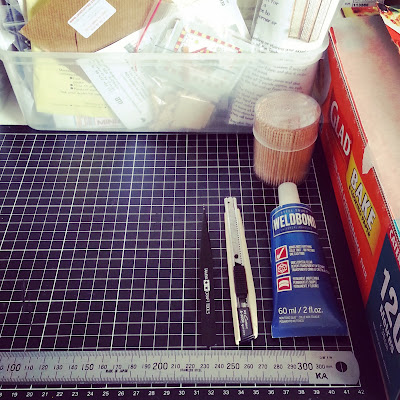 Cutting mat with a ruler, tweezers, cutting knife and tube of Weldbond glue arranged on it. To the right is a package of baking paper and to the back is a tub of miniature kits.